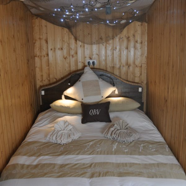 A bed in a wooden alcove with little lights above
