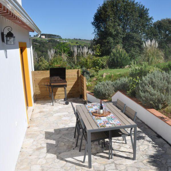 A garden table and BBQ on a sunny terrace